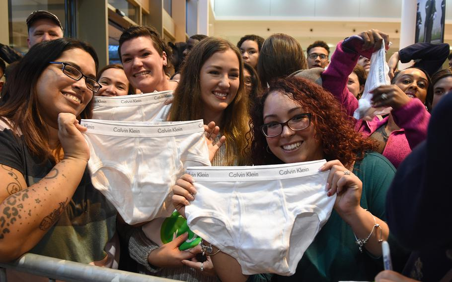 Military spouses Kristy Valentin, left, and Jennifer Spitznogle, right, hold up white Calvin Klein underwear they were hoping to get actor Mark Wahlberg to sign during his visit Sunday, Dec. 15, 2019, at Ramstein Air Base, Germany. Wahlberg famously modeled the underwear in his youth.