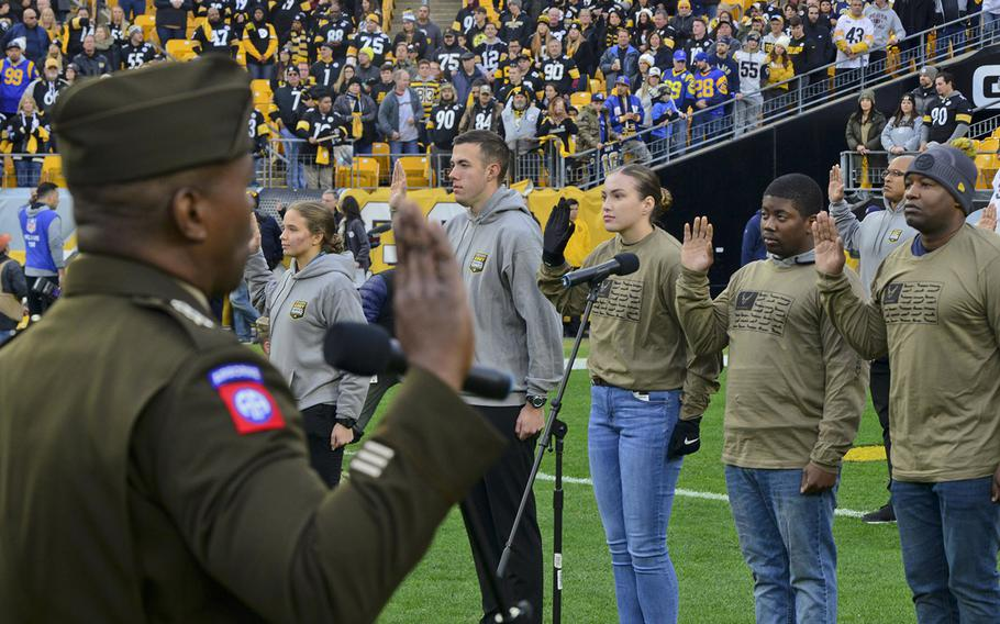Lt. Gen. Bruce Crawford, the Army's chief information officer, administers the oath of enlistment with more than 60 future soldiers, sailors and airmen during a mass joint-service swearing-in ceremony at Heinz Field in Pittsburgh on Nov. 10.