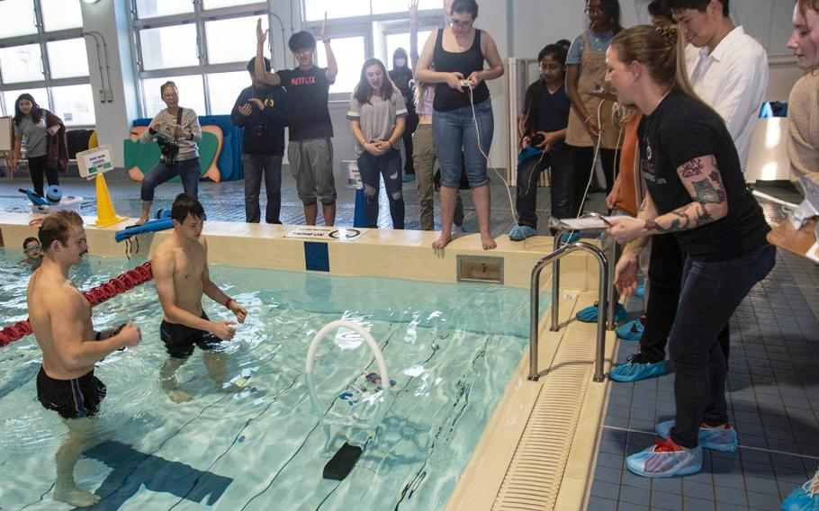 Students celebrate as their remotely operated underwater vehicle completes the final hurdle during a robotics challenge at Yokosuka Naval Base, Japan, Friday, Feb. 21, 2020.