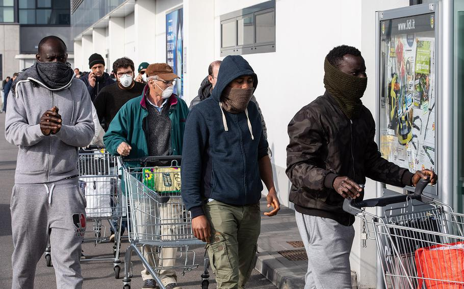 People wearing respiratory masks wait to be given a 10-minute access to shop in a LIDL supermarket in groups of 20 people on Sunday, Feb. 23, 2020 in Casalpusterlengo, southwest Milan, Italy.