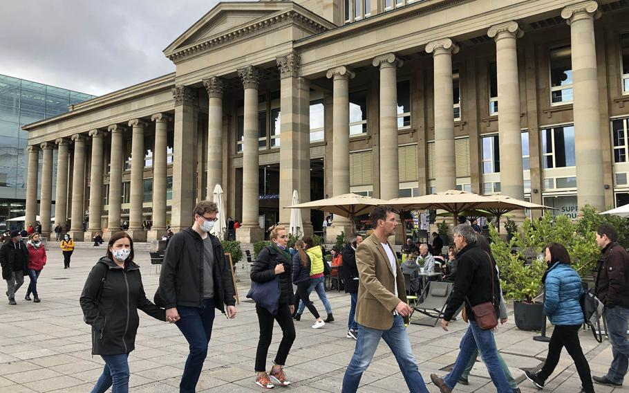 People walk in downtown Stuttgart on Monday, Oct. 12, 2020, hours after officials raised the health threat level to red following a sharp rise in the number of coronavirus cases. Face masks will be required in the city center starting Wednesday, as officials take steps to slow the spread of the virus.