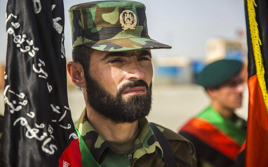 In a July 14, 2018 photo, an Afghan National Army soldier stands at attention during 2nd Kandak, 2nd Brigade's Operational Readiness Cycle graduation ceremony at Camp Shorabak in Helmand province.  Hundreds have died after the Taliban launched an offensive in the area in mid-October, leading the U.S. to conduct airstrikes against the militants, officials and news reports said on October 14, 2020.