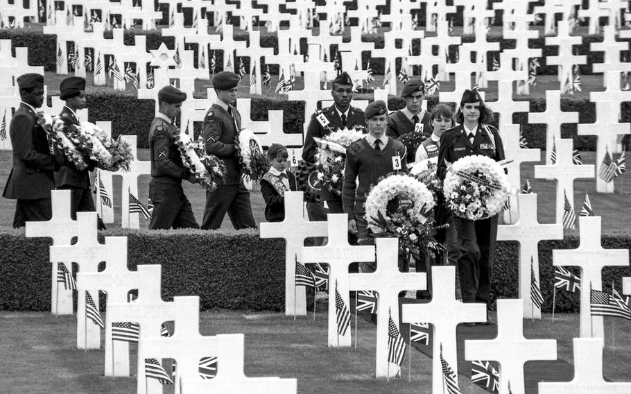 Representatives of various military services walk through the Cambridge American Military Cemetery with wreaths to honor the 3,812 fallen and 5,125 names on the Wall of the Missing in June, 1994.