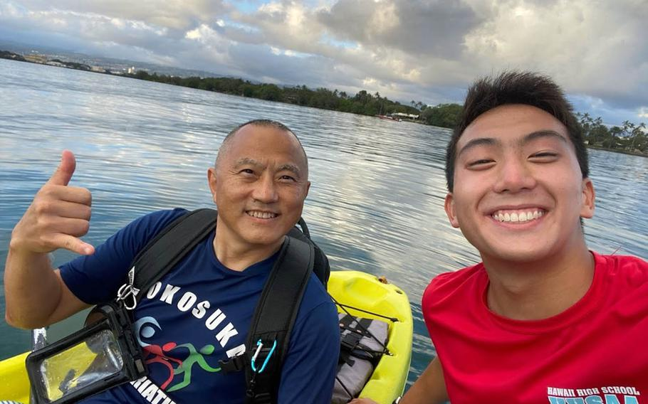 Jonah Lee, a senior at Radford High School, Hawaii, poses with his father, Navy Capt. Benjamin Lee, while kayaking at Pearl Harbor in this undated photo.