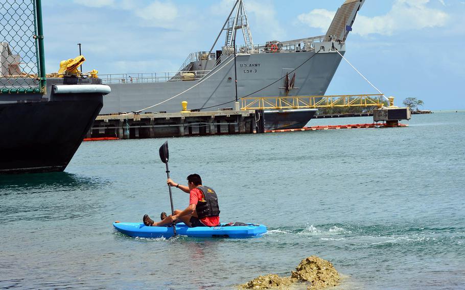 Jonah Lee, an 18-year-old high school senior in Hawaii, kayaks past Navy ships at Joint Base Pearl Harbor-Hickam, Hawaii, April 23, 2021.