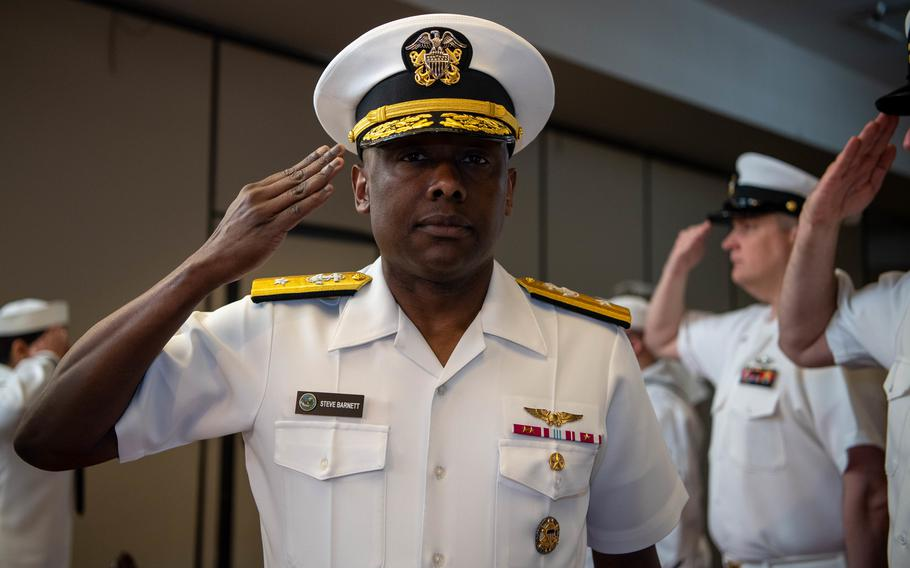 Rear Adm. Stephen Barnett renders a salute as he walks through sideboys during a change of command ceremony at Naval Base Kitsap-Bangor June 18, 2021.
