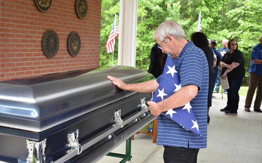 Thomas Staggs puts his hand on the casket of his friend, former Army Pfc. Thomas Bernard Winn, during his funeral on April 17, 2019, at the Central Louisiana Veterans Cemetery in Leesville. Winn died April 2 at age 65. The state was unable to identify any relatives, so the Louisiana Department of Veterans Affairs worked with local charities to bury Winn with full military honors and  to provide a funeral.