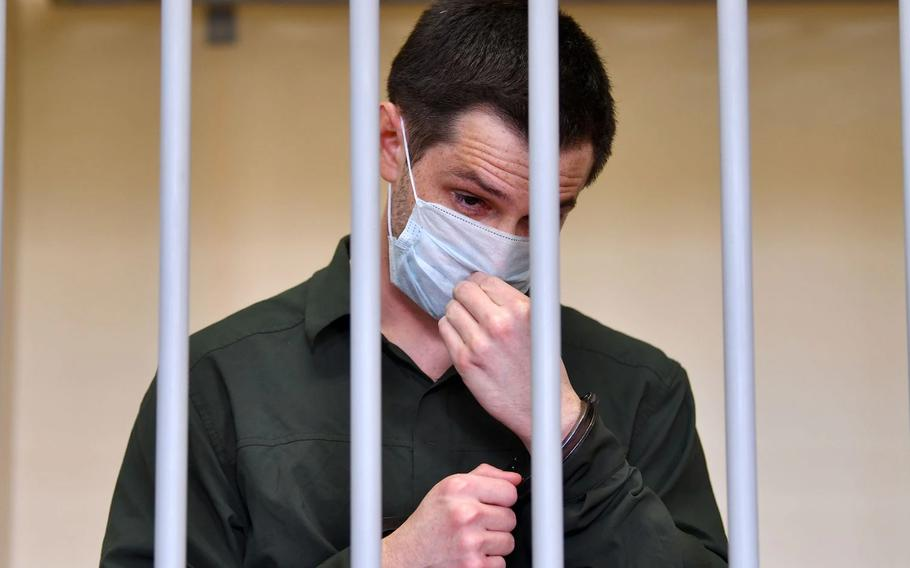 Former U.S. Marine Trevor Reed, charged with attacking police, adjusts his face mask while standing inside a defendants' cage during his verdict hearing at Moscow's Golovinsky district court on July 30, 2020.
