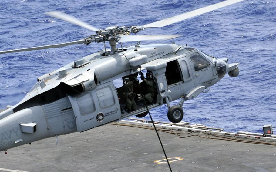 Sailors repel from an MH-60S Seahawk helicopter onto the flight deck of the aircraft carrier USS Abraham Lincoln in 2012.