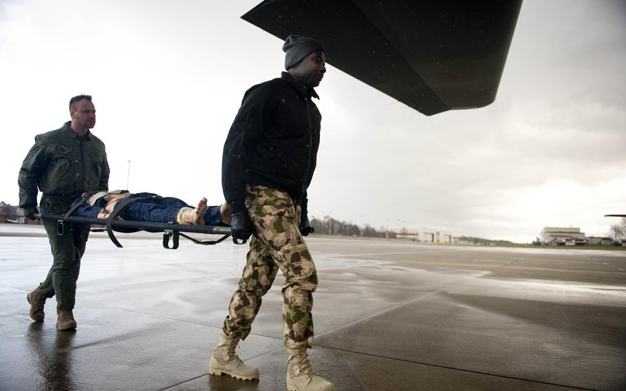 Nigerian Air Force Squadron Leader Benjamin Agom, right, and Slovenian Air Force 2nd Lt. Alvosa Lajbaher load a simulated patient onto a C-130J during aeromedical evacuation training at Ramstein Air Base, Germany, on Thursday, Jan. 18, 2018.