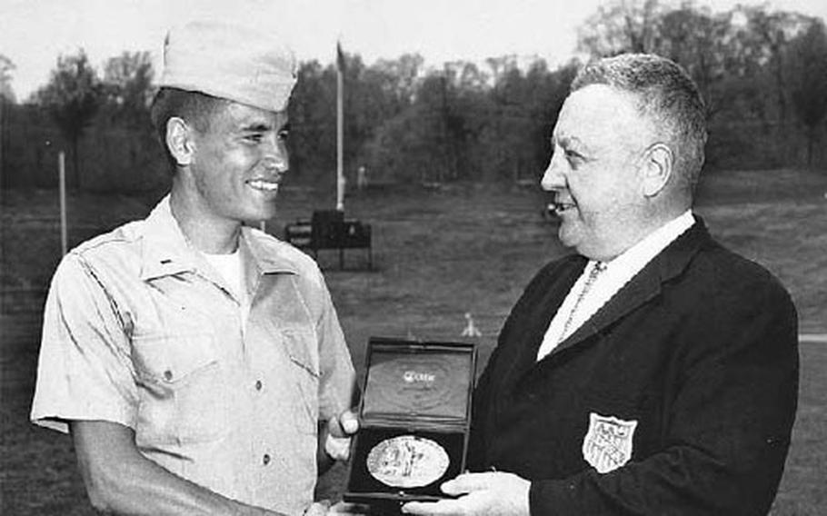 Capt. Stephen M. Archer, secretary of the AAU, presents Mills with the Charles J. Dieges Award.