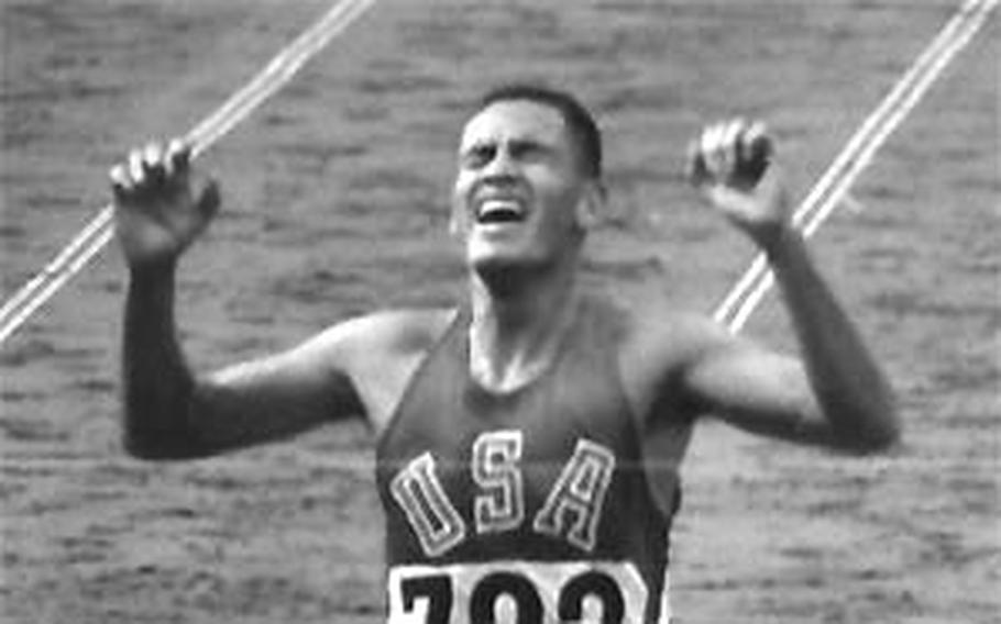 Billy Mills crosses the line with a win in the 10,000-meter race at the 1964 Olympics in Tokyo.