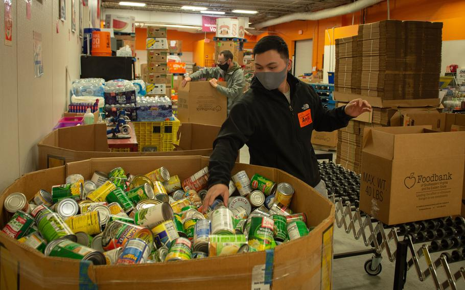 U.S. Navy Retail Service Specialist 3rd Class Anjo Balanza puts donated food items into boxes at the Foodbank of Southeastern Virginia and the Eastern Shore, in Norfolk, Virginia, April 1, 2021.