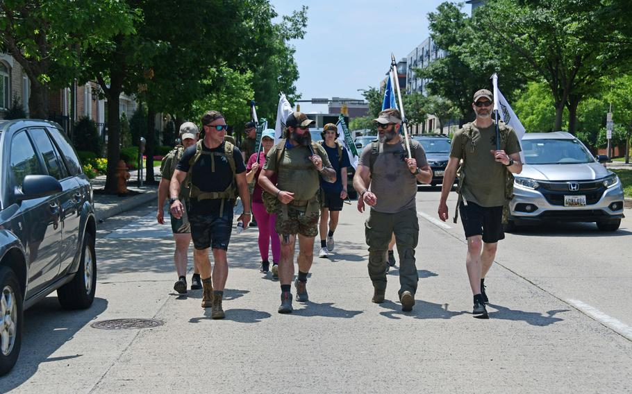 A group of active and retired military and active duty DEA Washington Field Division members walk on Key Highway to Federal Hill Park on Monday, June 7, 2021. They are raising money and awareness for APK Charities through the Ruck 2 Remember walk.