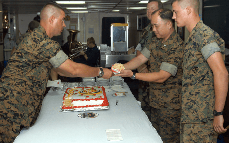 Col. Enrico DeGuzman, center right, is honored as the senior Marine at a cake-cutting ceremony in honor of the U.S. Marine Corps' 229th birthday aboard the USS Blue Ridge, the command ship of the Seventh Fleet, in 2004