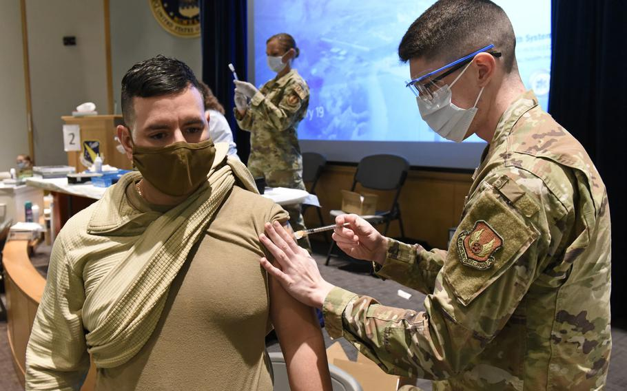 U.S. Army Sgt. 1st Class Joel Crespo a medic with the Lansing, Michigan Military Entrance Processing Station, receives the COVID-19 vaccine from Senior Airman Kody Phillips, a medical technician with the 88th Medical Group at Wright-Patterson Air Force Base, Ohio on Jan. 19, 2021.