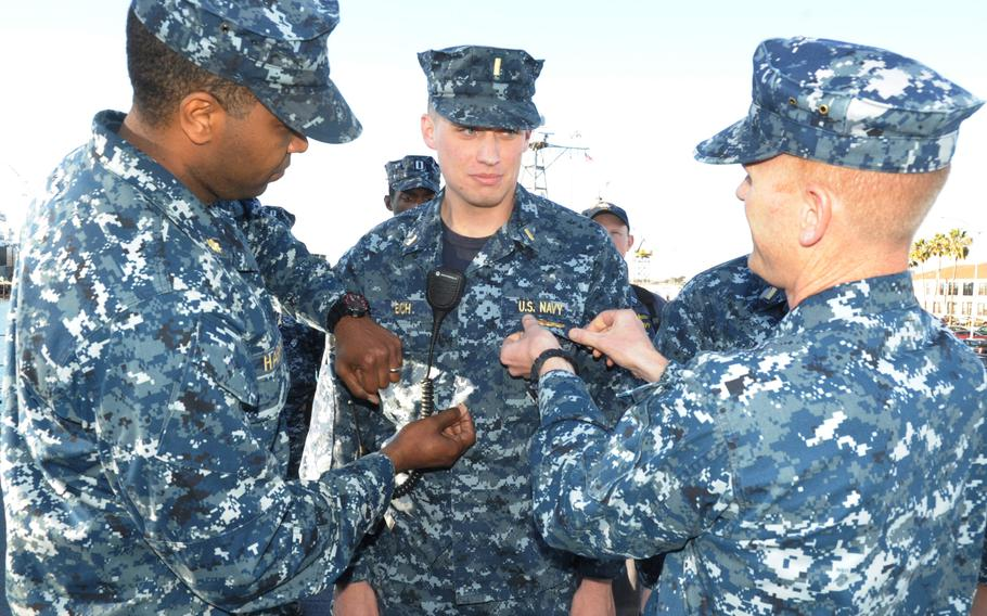A sailor receives his surface warfare officer pin during a ceremony aboard the littoral combat ship USS Freedom on Jan. 15, 2014.