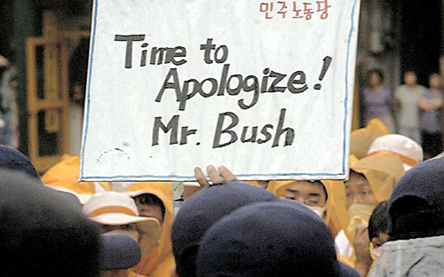 A protester holds a sign demanding an apology from U.S. President Bush outside Osan Air Base, South Korea, in August. More than 200 people gathered to protest a June 13 accident in which a U.S. Army vehicle crushed two South Korean girls.