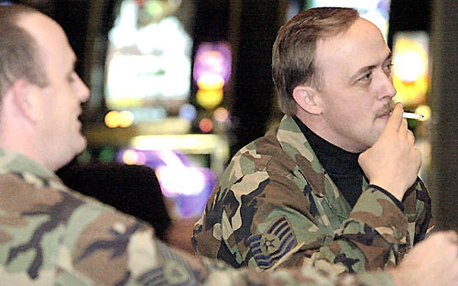 Air Force Tech. Sgt. Chris Preniss, left, and Tech. Sgt Damian Cone enjoy a smoke while watching college basketball at the Shogun Lounge in Yokota's enlisted club before a smoking ban at MWR facilities went into effect in December.