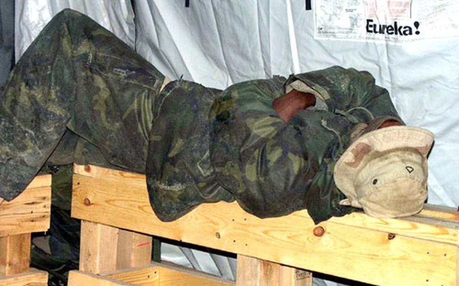Pfc. Latrell McCollins catches a quick nap during a break from installing a fuel supply system at Camp Virginia, Kuwait.