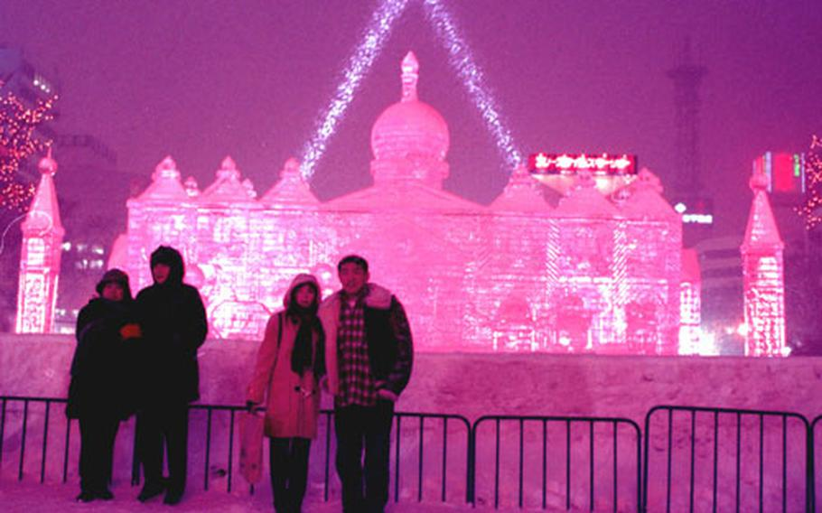 A European castle made entirely of ice shimmers in the night during the 1999 Sapporo Snow Festival.
