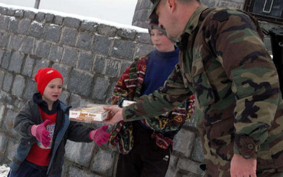 Spc. Kevin Bubb of C Company, 1st Battalion, 109th Infantry Regiment gives peanut butter cracker sandwiches to two Bosnian boys during a patrol through eastern Bosnia on New Year's Day. The boys turned in some rusty bullets to the soldiers.