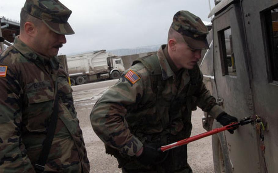 Spc. Kevin Bubb, left, and Sgt. Jon Clay, both of Company C, 1st Battalion, 109th Infantry Regiment try to break a frozen lock to get in their Humvees on Wednesday morning. The temperatures suddenly dropped overnight.