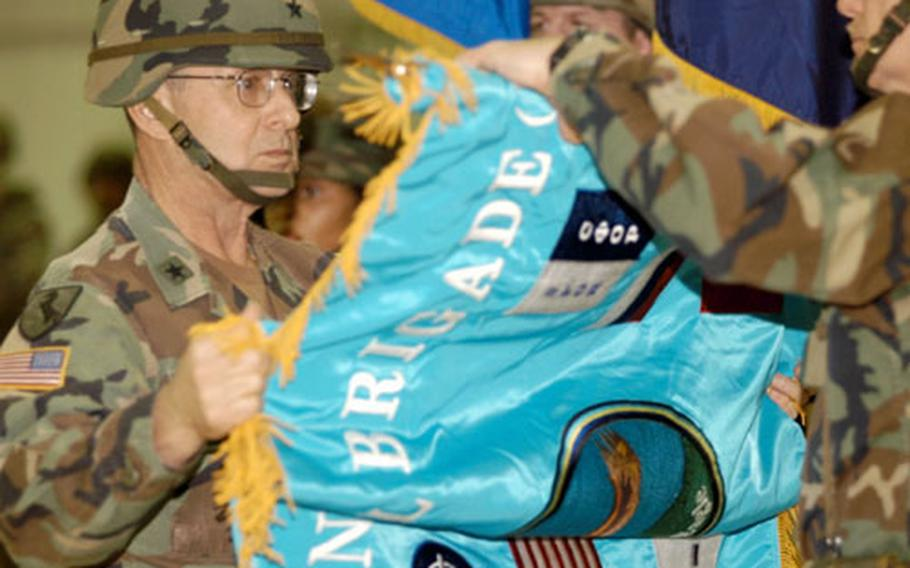 """Brig. Gen. John von Trott unrolls the new Multinational Brigade North flag. Multinational Division North officially changed the name to """"brigade"""" on Friday."""