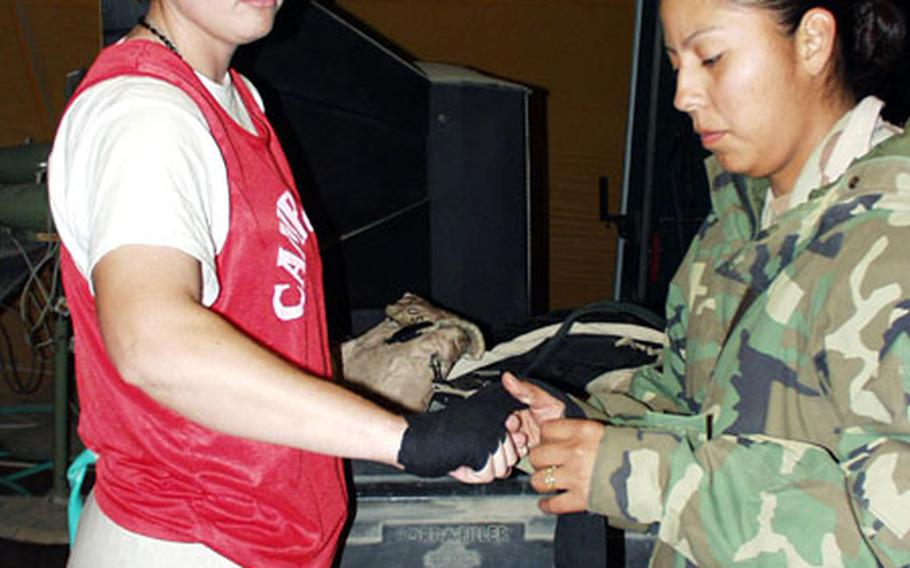 Sgt. Sharie Yellowhair wraps Sgt. Jessica Dull's hands in preparation for Dull's boxing match Saturday night at Camp New York, Kuwait.
