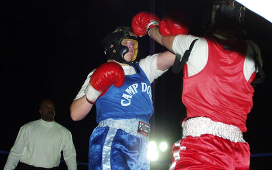 Spc. Jennifer Nelson, left, squares off with Sgt. Jessica Dull during a boxing match Saturday at Camp New York, Kuwait. Nelson and Dull were the only female soldiers who took part in the 13-match boxing tournament.