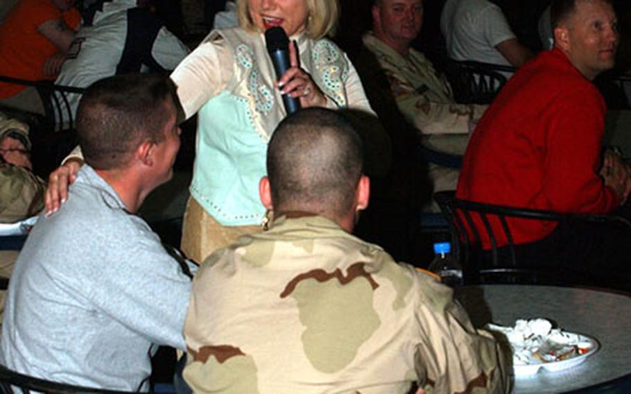 """Penny Gilley singles out two servicemembers during her show at Camp Doha, Kuwait, on Saturday night. Her show included a lot of crowd participation, as Gilley shook hands with audience members, sat in their laps and also let them sing into the microphone and finish the chorus to popular songs like """"Great Balls of Fire."""""""