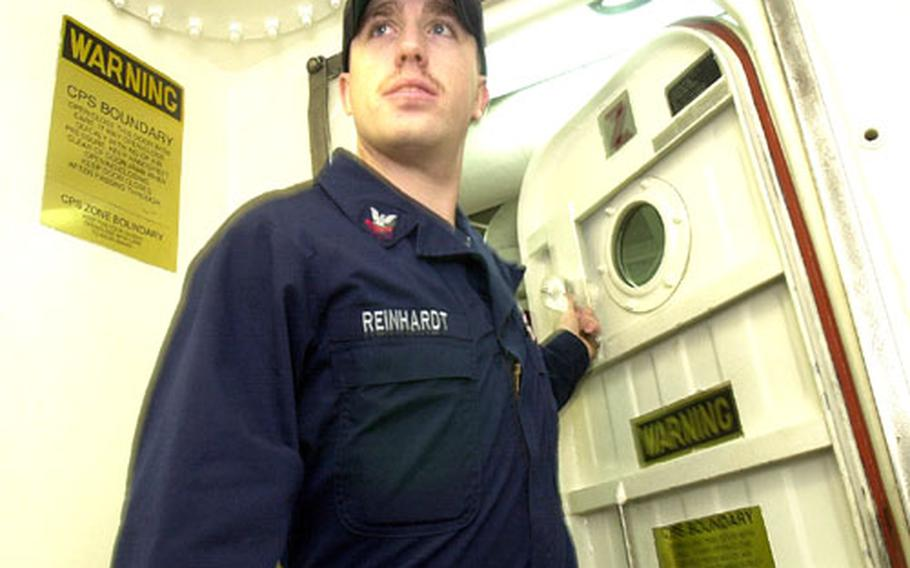Petty Officer 2nd Class Michael Reinhardt, a sailor aboard the USS John S. McCain, enters one of the ship's airlocks.