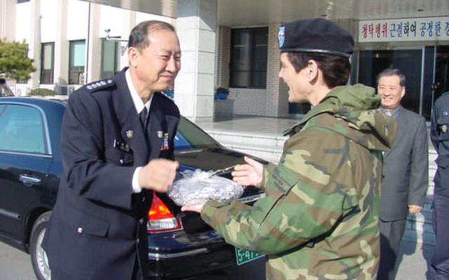 Police Chief Lee Kwang-young of the Korean National Police receives one of the 136 pies dropped off at Nambu police station in Taegu, South Korea by soldiers from U.S. Army installations in the city. Presenting Lee the pie is Army Maj. Gen. Jeanette K. Edmunds, commander of the 19th Theater Support Command at nearby Camp Henry. Edmunds, herself, baked several pies.