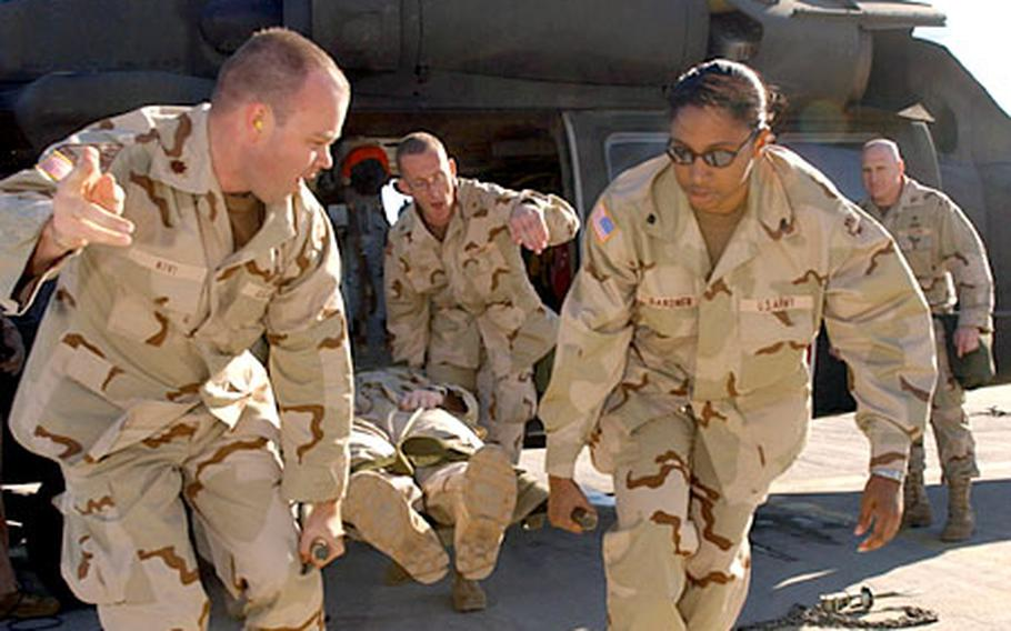Maj. Arno Kivi, left, and Spc. Xiomara Gardner, right, from the 865th Combat Support Hospital, unload a simulated casuality from a Black Hawk helicopter during a medical evacuation training exercise on Camp Doha, Kuwait. The hospital will operate a Level 3 medical treatment facility at Kuwait Armed Forces Hospital.