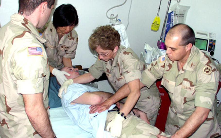 From left, Capt. Geoff Hobika, Col. Matilde Chua, Capt. Jane Schutz and Capt. Michael Pope learn how to roll over a trauma patient, played by Spc. Joseph Holcomb.