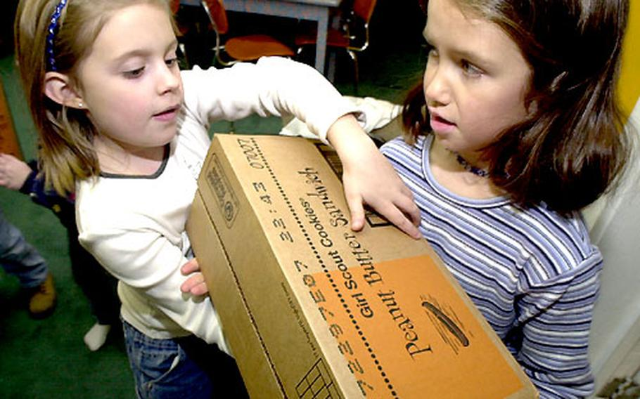 Allison Couch, left, and Melissa Patten lug boxes of Girl Scout cookies into the group's building at Atsugi Naval Air Facility, Japan, on Tuesday.
