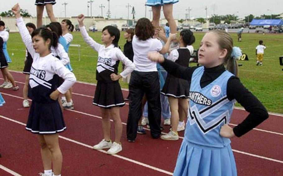 Cheerleaders from Kadena Youth Sports and Japanese girls from outside Kadena Air Base join together for first-of-its' kind cheerleading exchange during a football game Saturday on base.