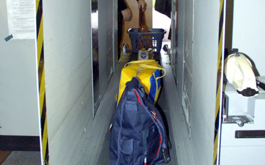 Passenger luggage runs through the X-ray machine at the Ramstein Air Base, Germany, before entering the terminal.