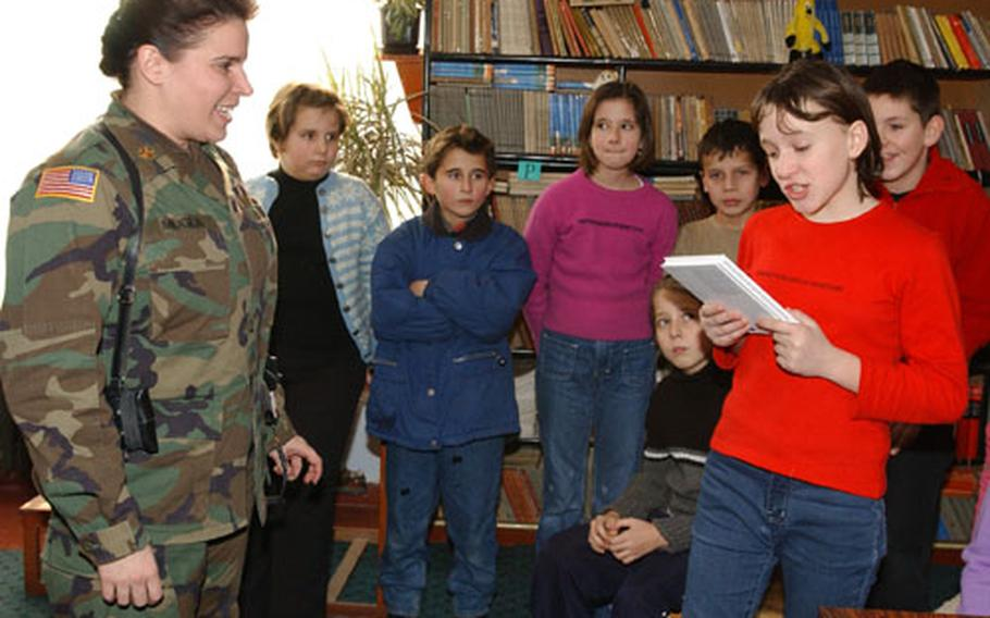 A fifth-grader at Tusanj Elementary School near Tuzla reads to Maj. Lauren Muglia of Headquarters and Headquarters Company, 28th Infantry Divsion, of the Pennsylvania National Guard, after Muglia delivered 31 books on Wednesday. Carolyn Muglia, Lauren's sister, her second-grade class, their parents and faculty from Watchung Elementary School in Middlesex, N.J., collected more than $350 for books on Bosnian school's mandatory reading list.