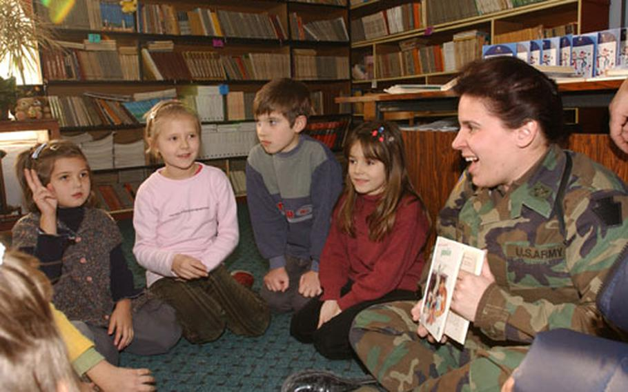 Maj. Lauren Muglia of Headquarters and Headquarters Company, 28th Infantry Divsion of the Pennsylvania National Guard, shows one of 31 books she delivered to Tusanj Elementary School on Wednesday to fifth-graders there.