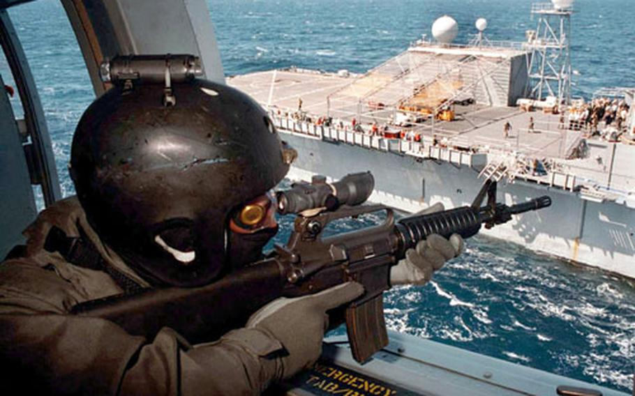 U.S. Navy Lt. Kevin McVadon from Great Falls, Virginia, assigned to Sea Air Land (SEAL) Team Eight, covers his squad from an SH-60 helicopter during a Helicopter Visit, Board, Search and Seizure (HVBSS) exercise on board Commander Sixth Fleet Command ship USS LaSalle (AGF 3) May 20, 1996.
