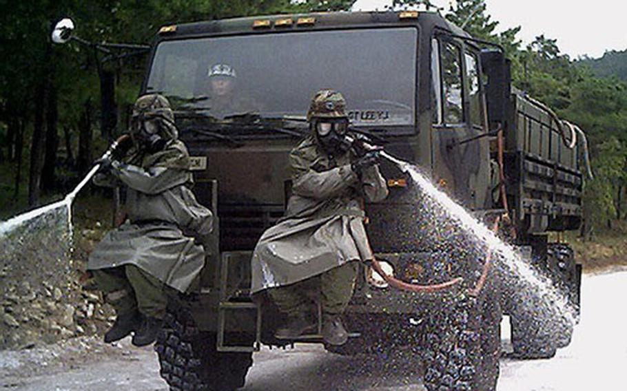 KATUSA soldiers of the U.S. Army's 23rd Chemical Battalion practice chemical decontamination of terrain, at Camp Carroll in Waegwan, South Korea.