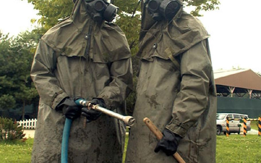 At Camp Carroll in Waegwan, South Korea, members of the Army's 23rd Chemical Battalion pose during demonstrations of battlefield decontamination methods held in July 2002.