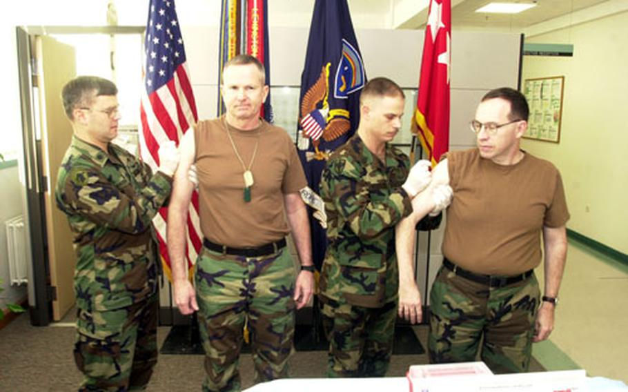 Gen. B.B. Bell, second from left, the commander of Army forces in Europe, and his top enlisted adviser, Command Sgt. Maj. David L. Lady, are the first two soldiers in Europe to recieve the smallpox vaccination Saturday.