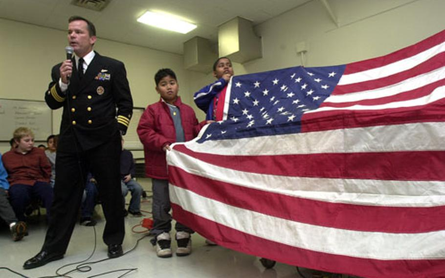 Cmdr. Seamus Flatley, commanding officer of Fighter Squadron 154, talks about Old Glory, a special American flag on a world tour, Friday at Shirley Lanham Elementary School on Naval Air Facility Atsugi, Japan.
