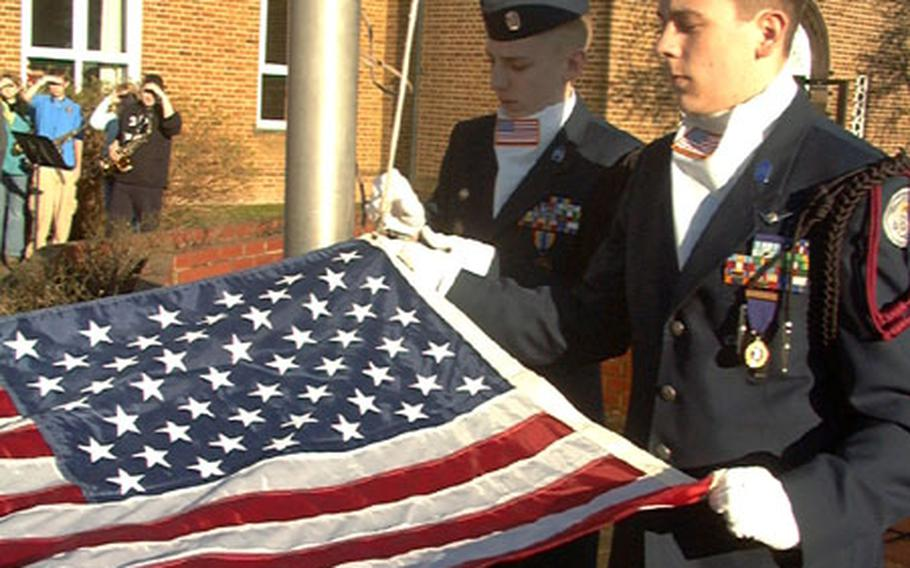 Trey Vickroy, right, and Scott Millard, cadets with the Air Force JROTC at Lakenheath High School, prepare to raise a flag Monday at Lakenheath Middle School on RAF Feltwell, England. The flag was flown above the Pentagon on the first anniversary of the terrorist attacks of September 2001.