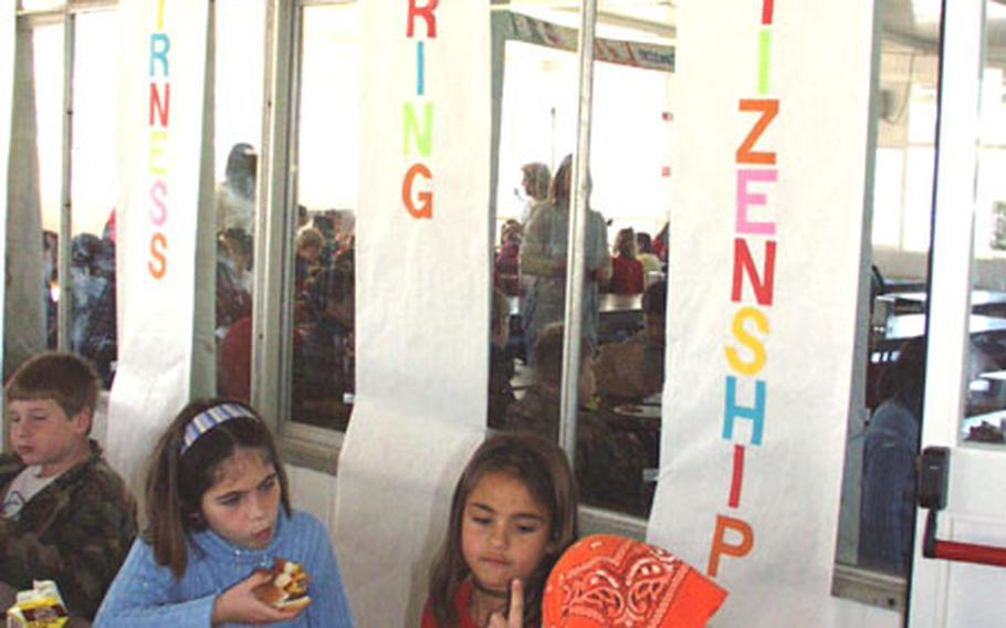 """Third-graders Alisha Schiermeyer, Alyssa Toney, and Tamela Queen eat lunch Monday at Naval Station Rota, Spain, in front banners signifying three of the six pillars of character. The base's elementary school along with all Defense Department schools in the Mediterranean School District have adopted """"Character Counts!"""" The character-building program is popular among schools in the United States."""