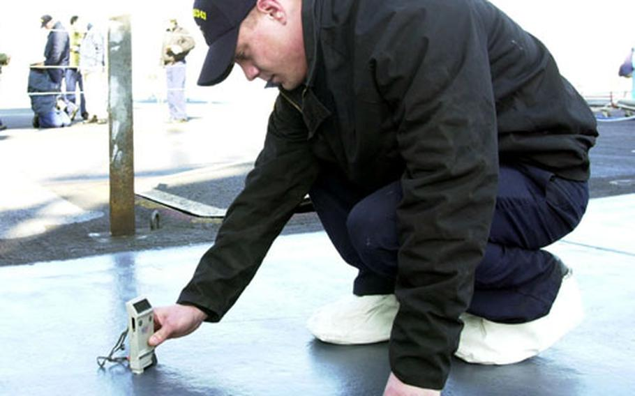 Airman Stephen Lutz, a quality assessor on the USS Kitty Hawk, checks the thickness of paint applied to the flight deck Monday after the crew had applied layers of paint and a new, non-skid surface.
