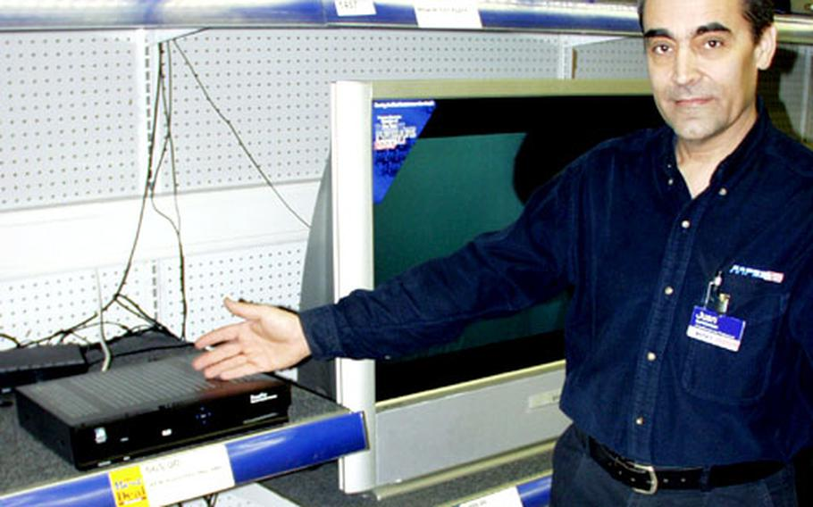 Army and Air Force Exchange Service supervisor Juan Quenonas shows a $565 decoder that is needed to descramble AFN shows that are broadcast via satellite. The U.S. European Command is working on a plan to provide the equipment for free to servicemembers and Department of Defense civilian employees.