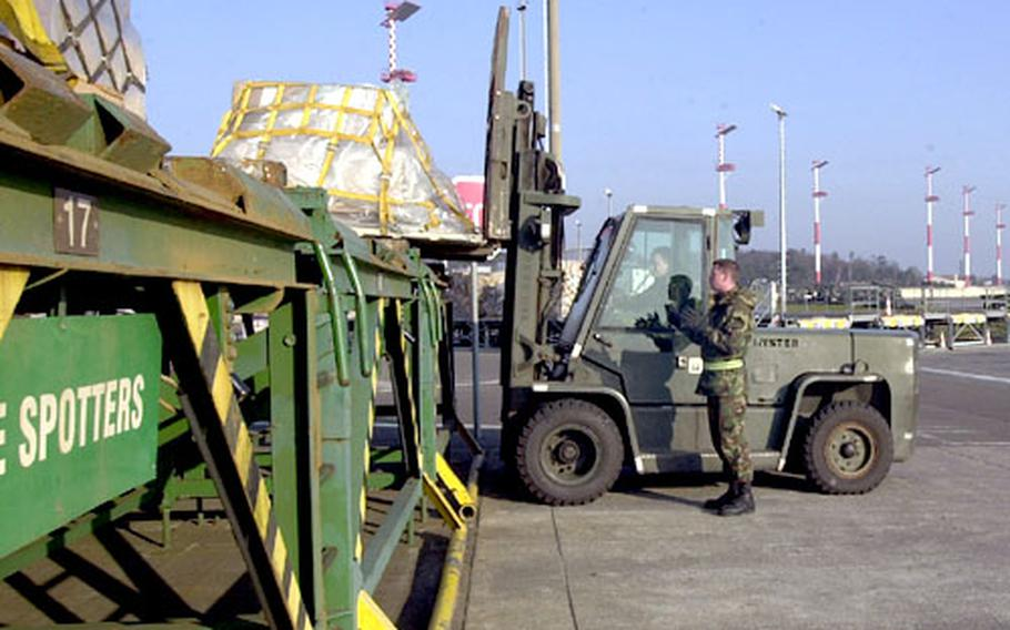 Senior Airman Paul Franklin of the 723rd Air Mobility Squadron at Ramstein Air Base, Germany, directs Staff Sgt. Matthew Huffman as he loads equipment for transportation to a cargo aircraft. The Ramstein flight line has remained busy over the past year, according to wing officials, and the end is nowhere in sight.